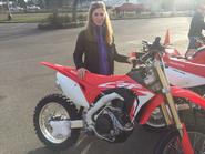 Vicki Gray standing beside a Honda dirt bike image